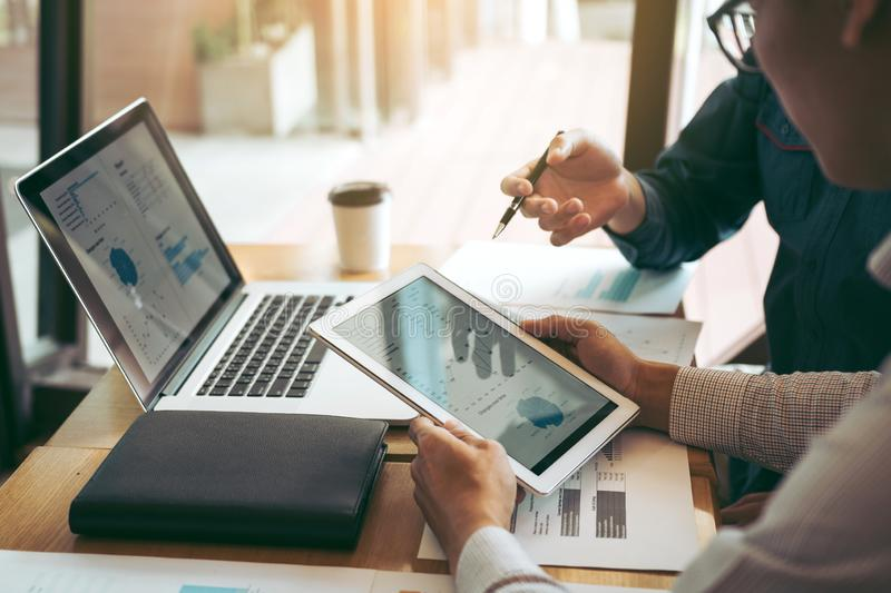 Business partnership coworkers using a tablet to chart company financial statements report and profits work progress and planning royalty free stock photo