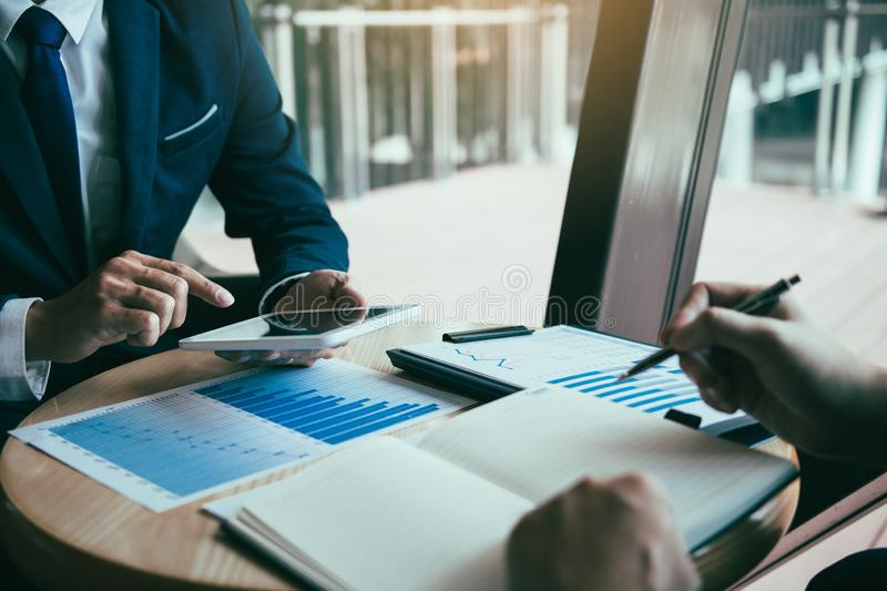 Business partnership coworkers using a tablet to chart company financial statements report and profits work progress and planning. In office room royalty free stock images