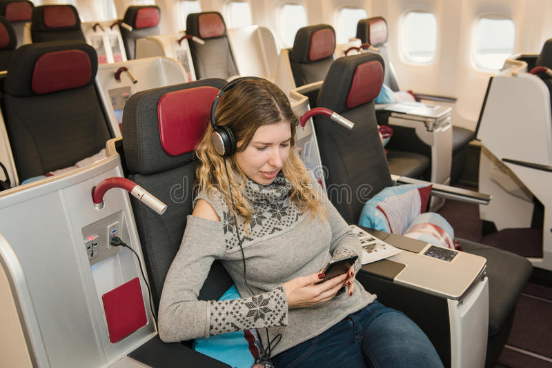 Business passenger listening to music and relaxing during the fl. Business woman passenger listening to music and relaxing during the flight by airplane in first royalty free stock photos