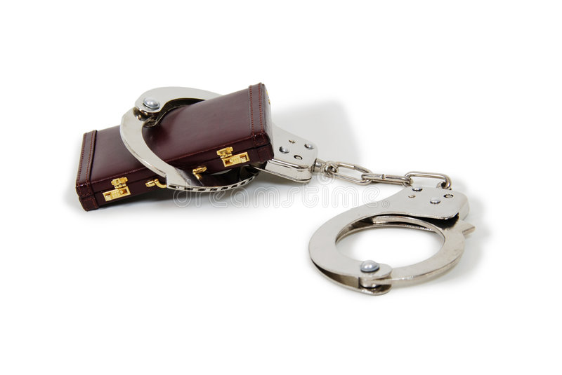 Business Penalties. Handcuffs made of metal with mechanical clasp on burgandy leather briefcase royalty free stock image