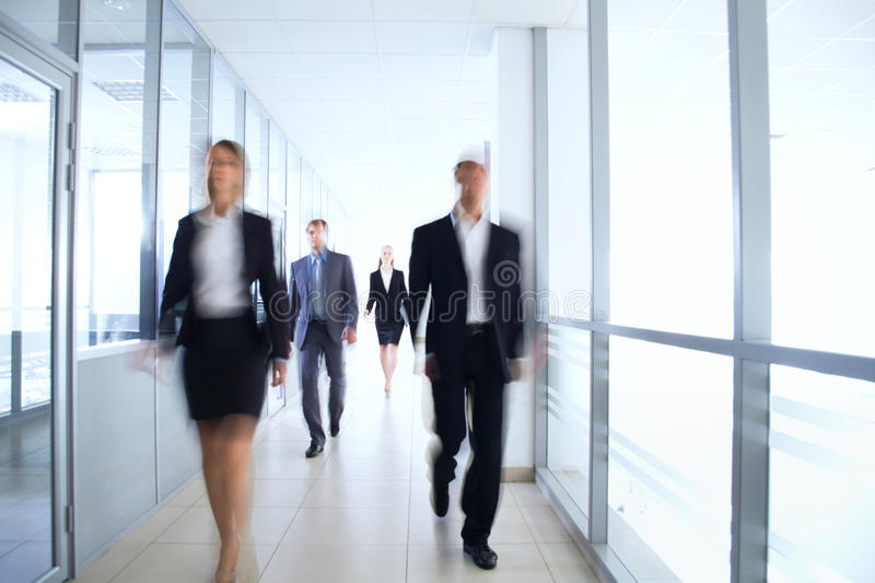 Business people. Walking in the office corridor stock images