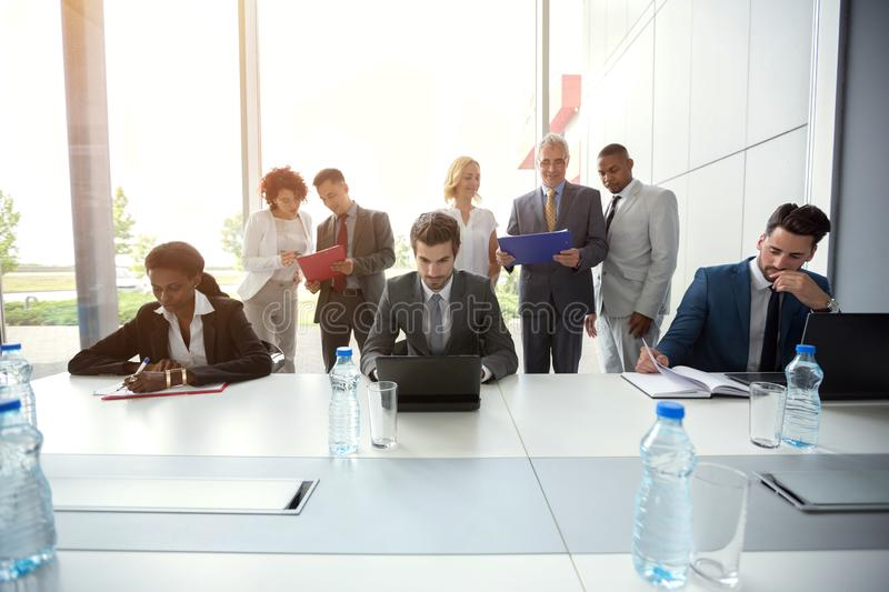 Business people analyzing management. Business people analyzing company management on meeting stock photography