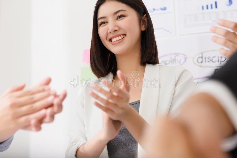 Business people applauding at conference after dealing and signing contract or agreement with partners abroad. Asian businesswoman applauding and happy smile stock photography