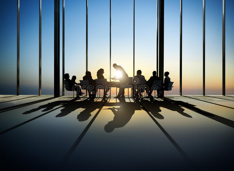 Business People Around The Conference Table. Group of business around the conference table with a view of sunset stock photos