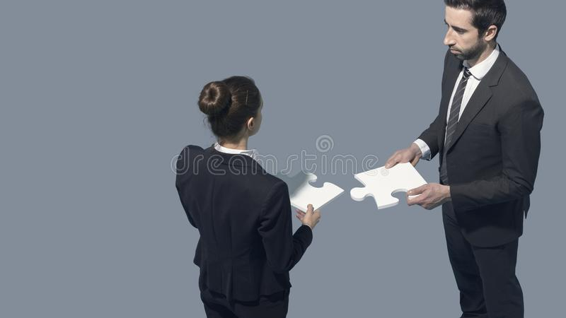 Business people assembling a jigsaw puzzle stock image
