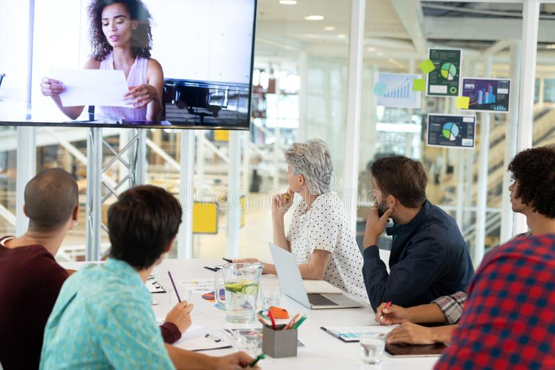 Business people attending video conference at conference room in a modern office. Rear view of diverse business people attending video conference at conference royalty free stock photos