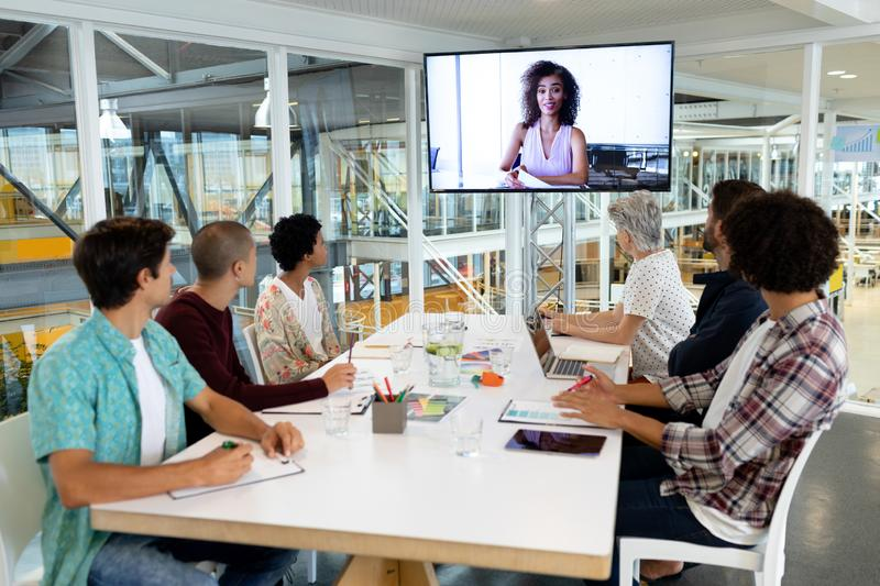 Business people attending video conference at conference room in a modern office. Rear view of diverse business people attending video conference at conference stock photos
