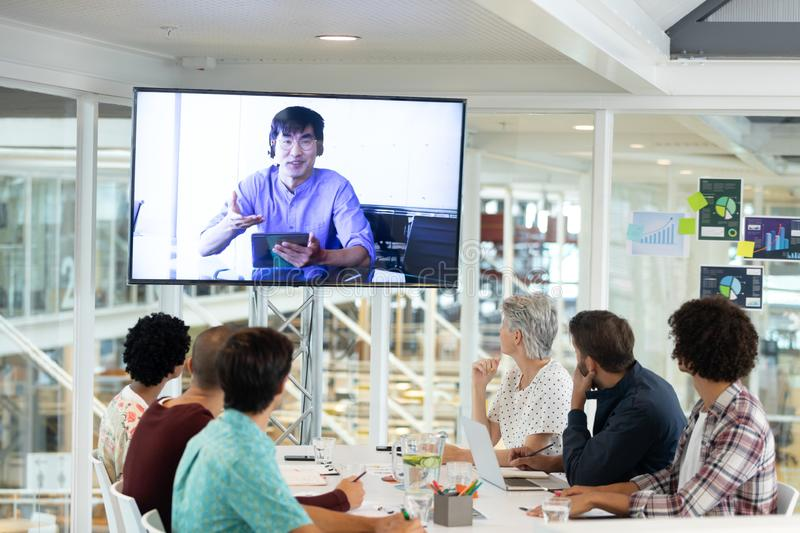 Business people attending video conference at conference room in a modern office. Rear view of diverse business people attending video conference at conference royalty free stock images