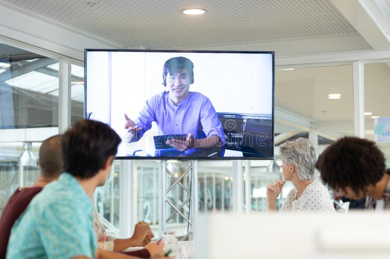 Business people attending video conference at conference room in a modern office. Rear view of diverse business people attending video conference at conference royalty free stock image
