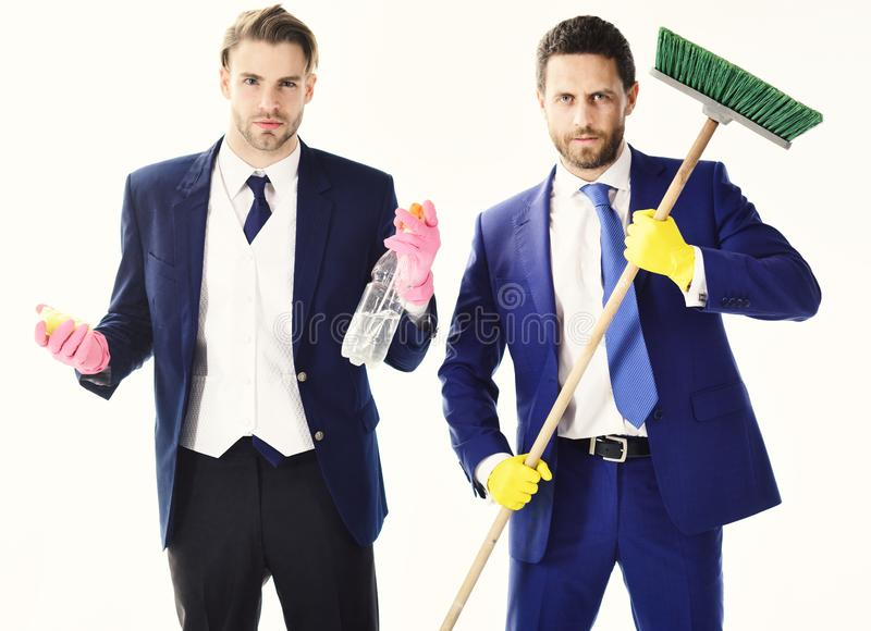 Business people with beards and mop. Bearded friends in formal suits with serious faces and sweep. Housework, cleaning. Business, teamwork, support concept stock images