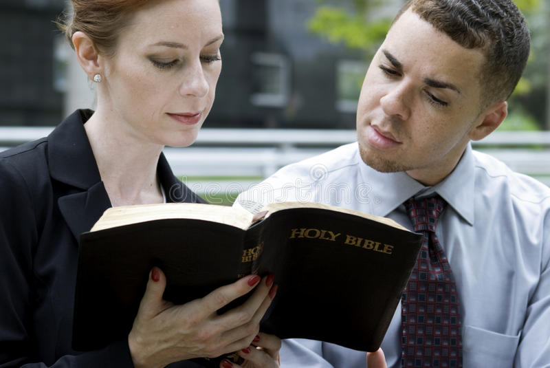 Business People and The Bible. Two Christian coworkers sitting outside reading from the Holy Bible perhaps on their lunch break stock photo