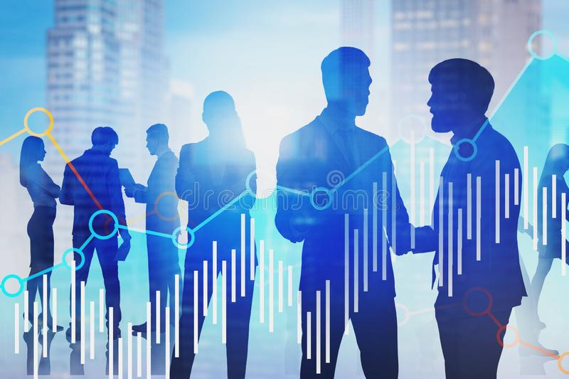 Business people in blurred city, graphs. Silhouettes of business people shaking hands and discussing documents in blurred city with double exposure of graphs stock image