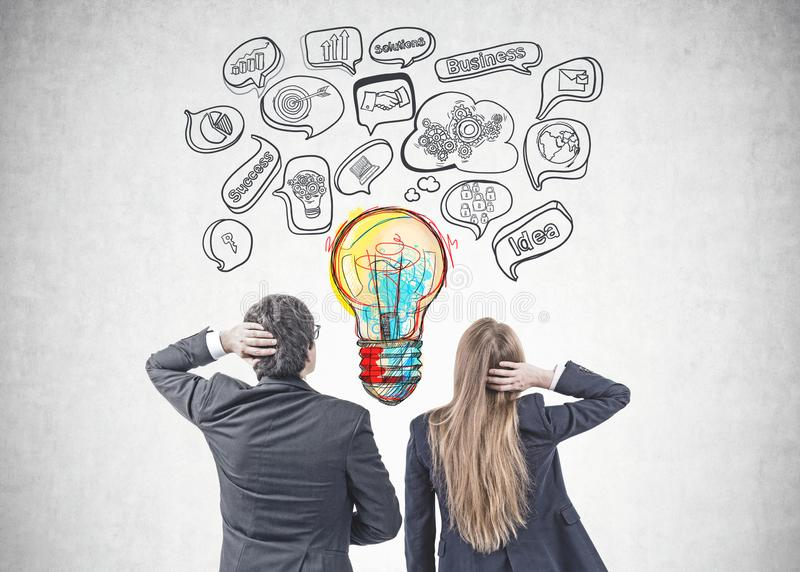 Business people brainstorming for best idea. Rear view of young caucasian businessman with black hair and his blonde colleague wearing a dark suits and royalty free stock image