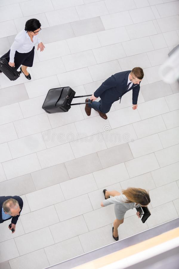 Business people with briefcases walking in office lobby. High angle view of business people with briefcases walking in office lobby royalty free stock photography
