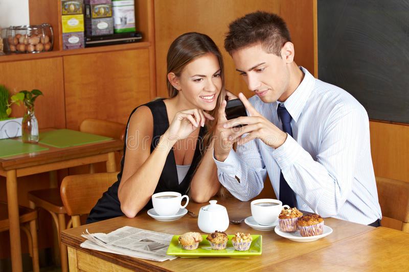 Business people in café. With smartphone having a meeting stock photography