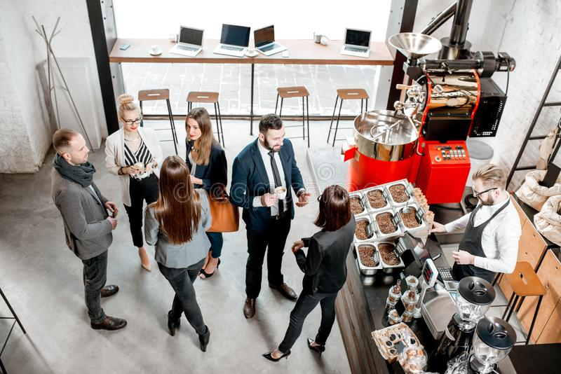 Business people in the cafe. Business people talking and having fun durnig a coffee time in the modern cafe interior. Wide view from above stock images