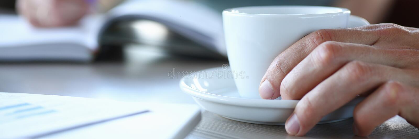 Business people in cafe coffee break at table hold cup of coffee in arm royalty free stock photography