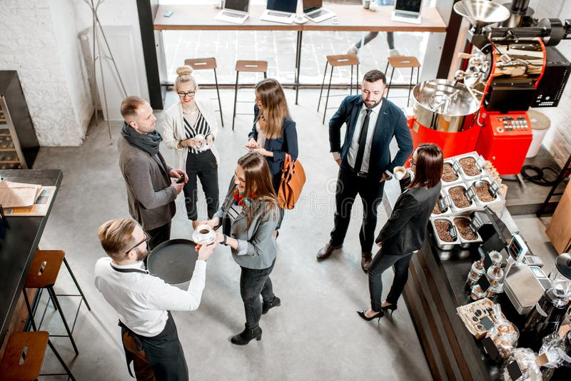 Business people in the cafe. Business people talking and having fun durnig a coffee time in the modern cafe interior. Wide view from above royalty free stock photography