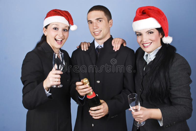 Business people celebrate Christmas. With champagne and wearing Santa hats and laughing together on blue background,check also stock photos
