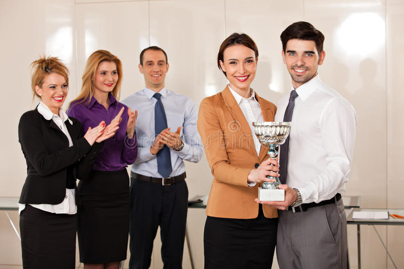 Business people celebrating their victory. Young couple holding a trophy; happy business people celebrating their victory, applauded by their partners stock photos