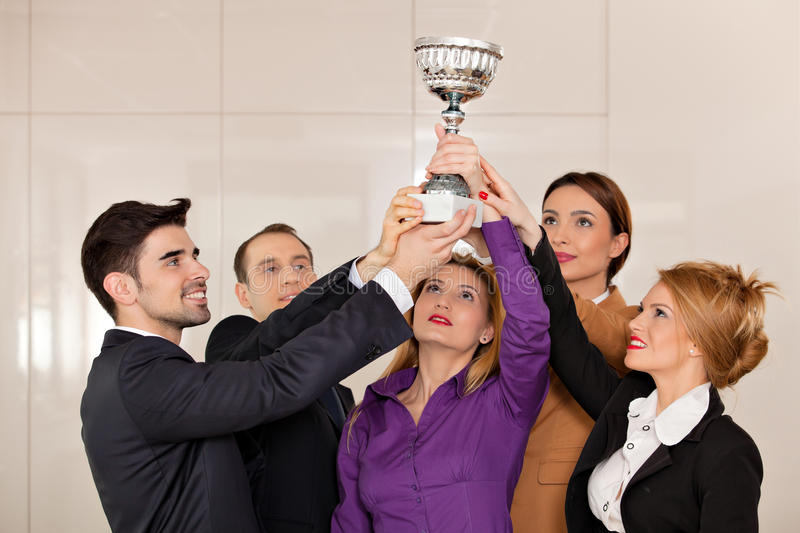 Business people celebrating victory. Young team holding a trophy; happy business people celebrating their victory stock photography