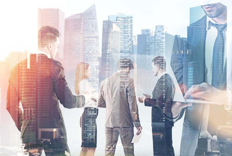 Business people in a city. Business people talking to each other agarinst a modern cityscape background. Communication concept. Toned image double exposure royalty free stock images