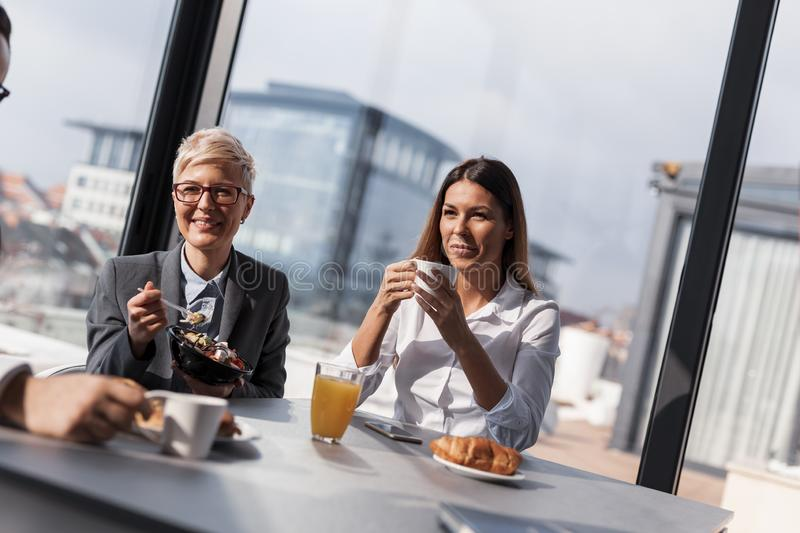 Business people on a coffee break. Group of business people on a coffee break in company`s restaurant stock photo