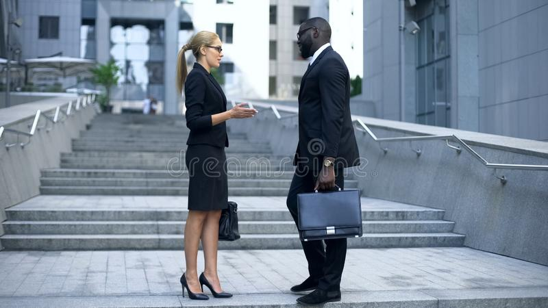 Business people communicating near office center, sharing news, partnership. Stock photo stock images