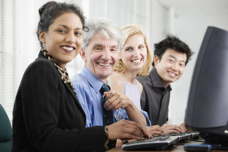 Business people on computers. Portrait of business executives sitting at computers stock photo