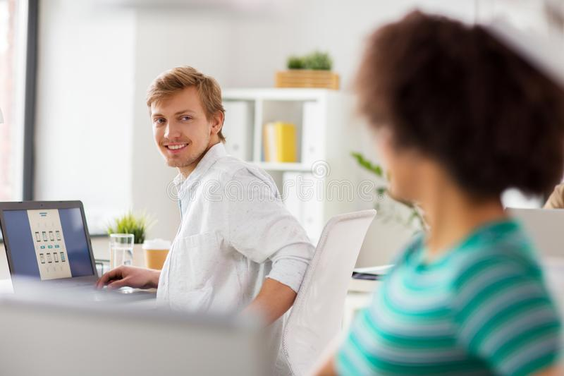 Happy creative workers with laptops at office royalty free stock photo