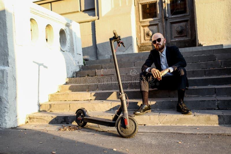 Business and people and concept - jeune homme d'affaires qui fait du scooter électrique en plein air photo stock