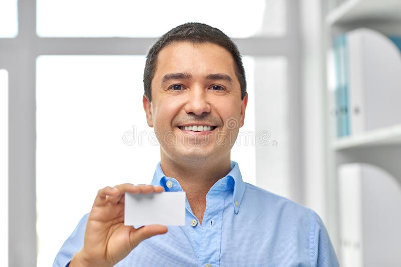 Smiling businessman with business card at office royalty free stock photos