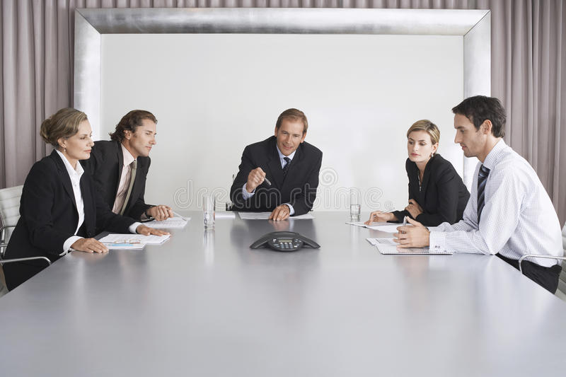 Business People On Conference Call. Group of business people on conference call in boardroom royalty free stock image