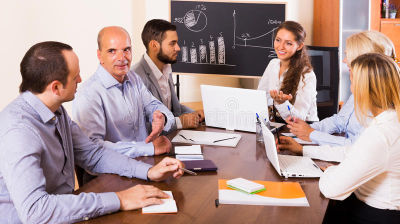 Business people during conference call. Positive young business people during conference call indoors stock photography