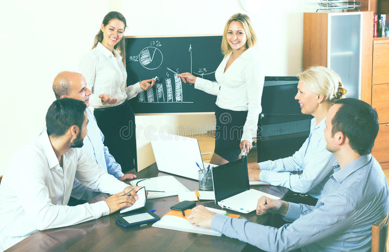 Business people during conference call. Successful smiling adult business people during conference call indoors royalty free stock image