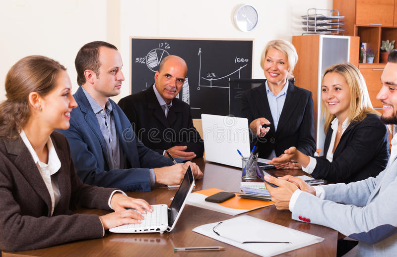 Business people during conference call. Successful smiling young business people during conference call indoors royalty free stock photos