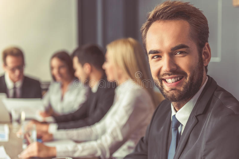 Business people at the conference. Business people in formal wear are discussing affairs at the conference. Handsome men in the foreground is looking at camera royalty free stock photo