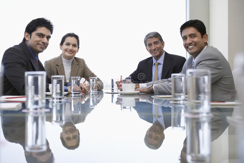 Business People At Conference Table. Portrait of Indian business people sitting at conference table stock images