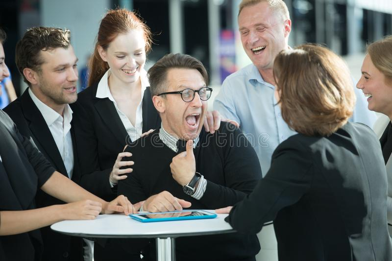 Business people congratulating coworker stock photos