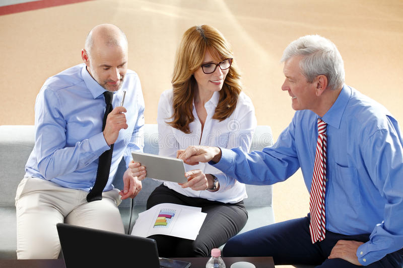 Business people consulting. Image of middle age businesswoman holding digital tablet while sitting at office with businessmen and consulting from financial plan stock photography