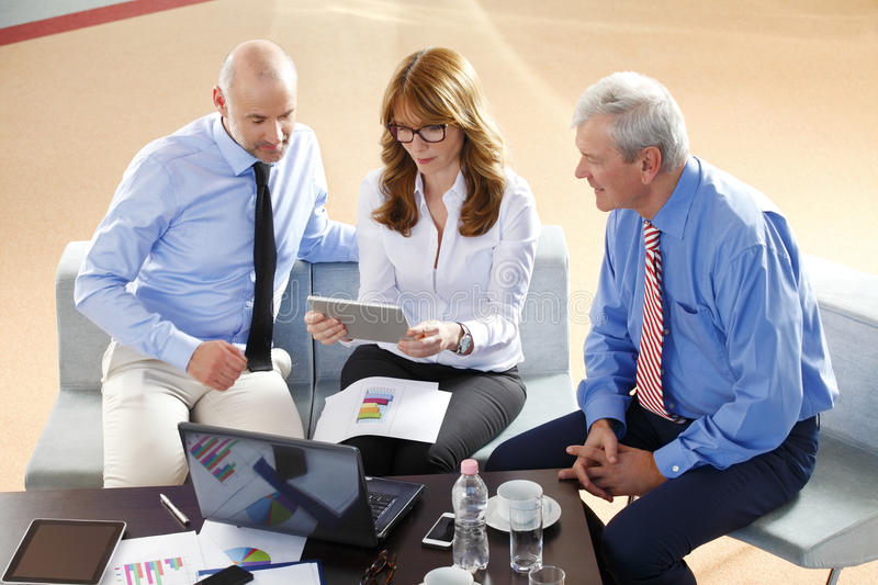 Business people consulting. Image of middle age businesswoman holding digital tablet while sitting at office with businessmen and consulting from financial plan royalty free stock photos