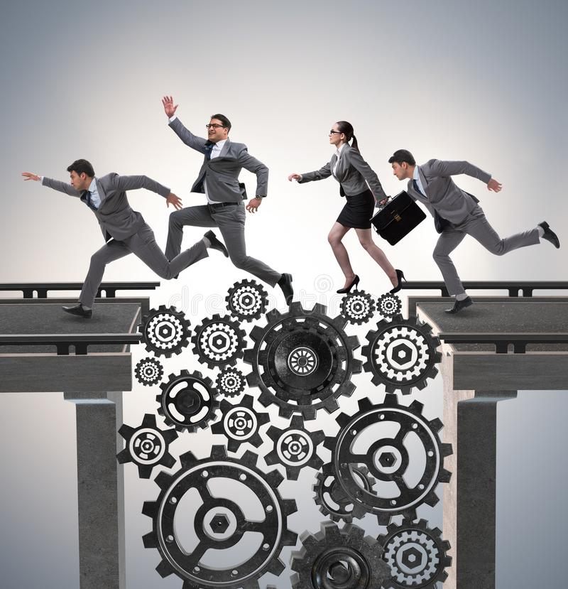 Business people crossing the bridge with cogwheels royalty free stock image