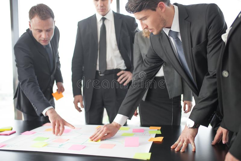 Business people developing plan on office desk. Business people team developing plan on office desk using stick notes royalty free stock photo
