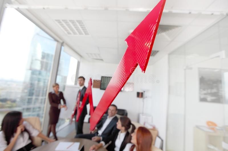 Business people and income growth. Business people discuss red arrow of income growth at meeting royalty free stock photography
