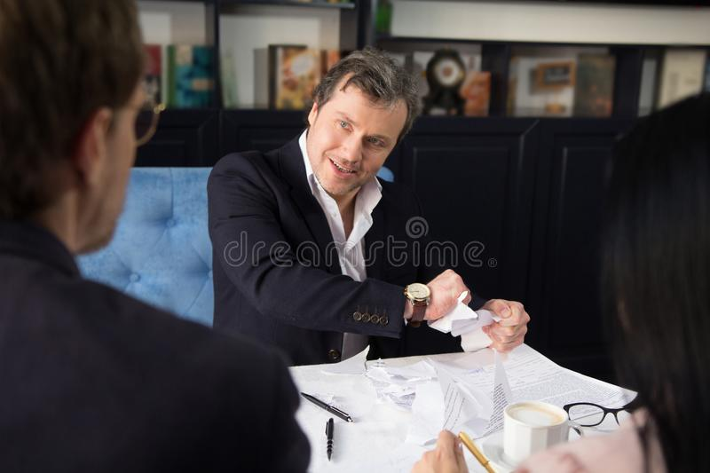 Business people discussing agreement condition. Tense situation between partners. One of them torning agreement stock photography