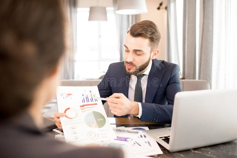 Business people discussing analytical data. Serious confident business analyst explaining graphs and pointing at paper while presenting report to colleague at royalty free stock image