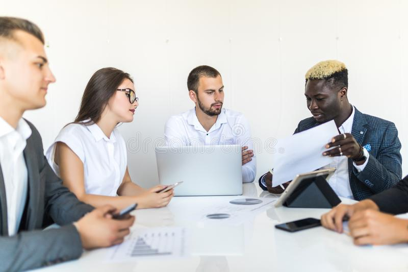 Business people discussing the charts and graphs showing the results of their successful teamwork, multi ethnic business. Business royalty free stock images
