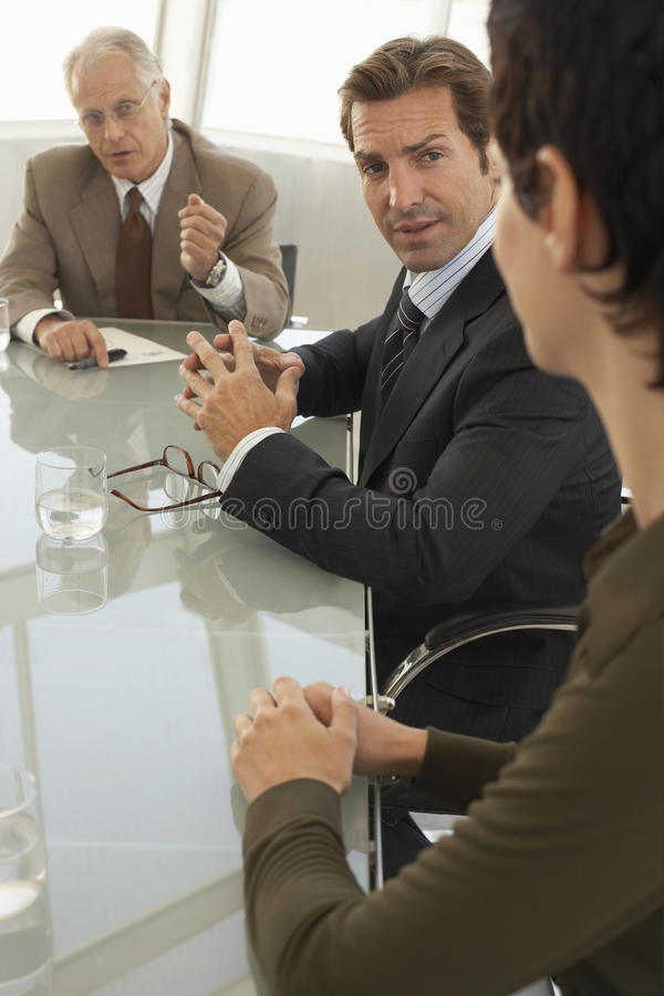 Business People Discussing In Conference Room. Senior businessman discussing with colleagues in conference room stock photo