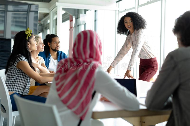 Business people discussing with each other at conference room in a modern office. Front view of diverse business people discussing with each other at conference royalty free stock photography