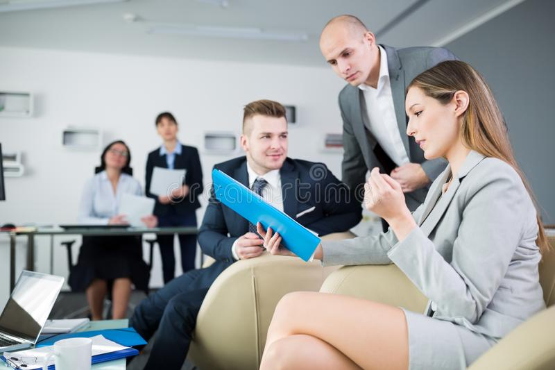 Business People Discussing Over Clipboard In Office stock image